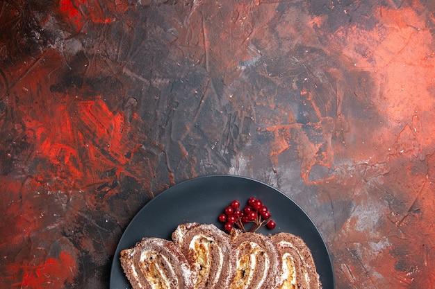 Top view yummy biscuit rolls with fruits on dark floor