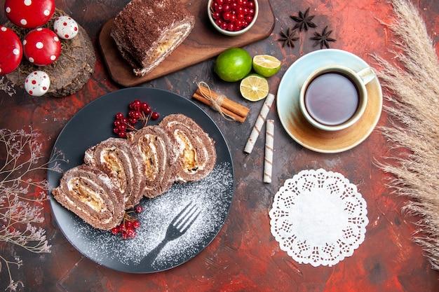 Vista dall'alto gustosi rotoli di biscotti con tè su sfondo scuro