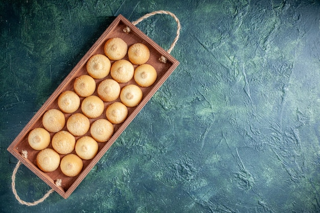 Top view yummy biscuits inside wooden box on dark blue background sugar cookie biscuit cake pie color sweet nut tea free space