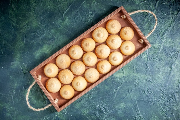 Top view yummy biscuits inside wooden box on a dark blue background sugar cookie biscuit cake pie color sweet nut tea