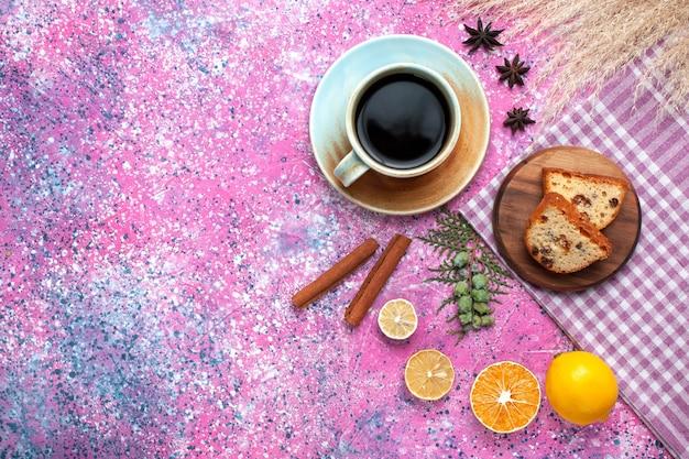 Vista dall'alto di una deliziosa torta a fette con una tazza di tè al limone e cannella sulla superficie rosa