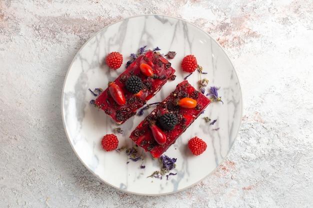 Torta gustosa vista dall'alto fette torta di bacche con crema e frutti di bosco su fondo bianco