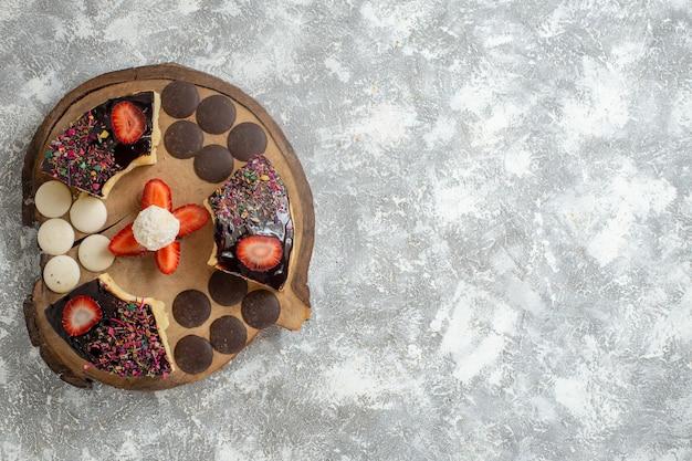 Fette di torta gustosa vista dall'alto con biscotti al cioccolato sulla superficie bianca