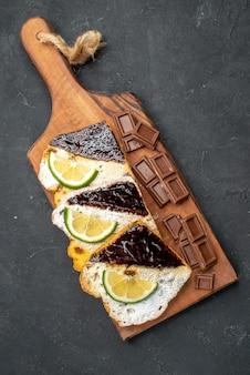 Vista dall'alto gustose fette di torta con barrette di cioccolato sulla superficie scura