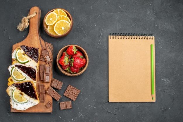 Fette di torta gustosa vista dall'alto con cioccolato e frutta sulla superficie scura