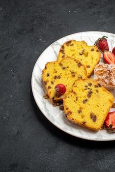 灰色の表面に新鮮な赤いイチゴとクッキーが付いた上面図のおいしいケーキスライス