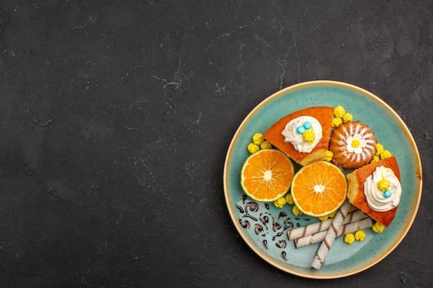 Вид сверху кусочками вкусного торта с трубочным печеньем и нарезанными мандаринами на темноте