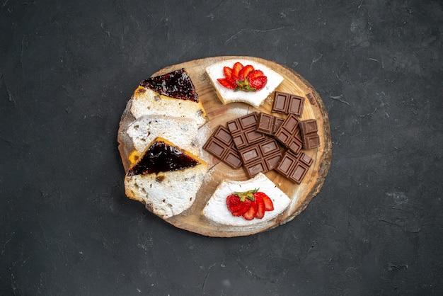Вид сверху кусочками вкусного торта с клубникой и шоколадными батончиками на темной поверхности