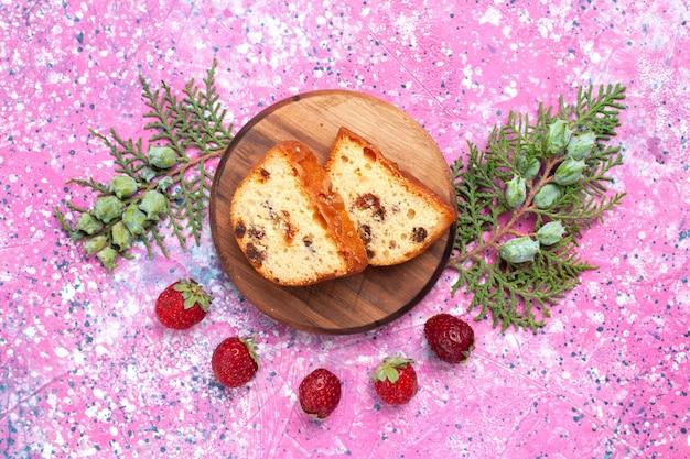 Vista dall'alto di una deliziosa torta dolce e gustosa a fette con fragole rosse fresche sulla superficie rosa