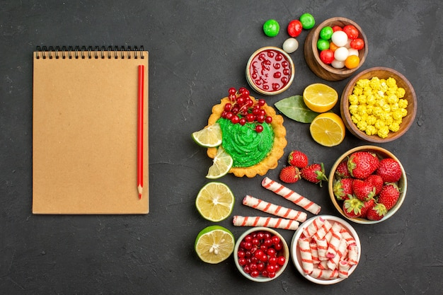 Top view yummy cake with candies and fruits on dark background cookies biscuit sweet