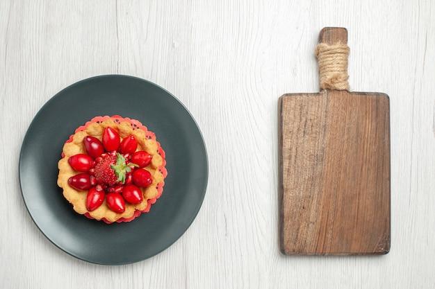 Torta gustosa vista dall'alto con frutta fresca all'interno del piatto sullo scrittorio bianco chiaro
