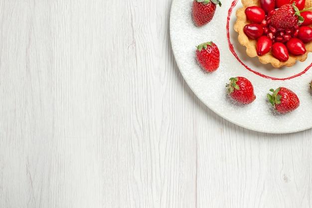 白い机の上のプレートの中に新鮮な果物とトップビューおいしいケーキ