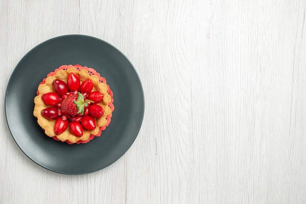 Вкусный торт со свежими фруктами внутри тарелки на белом столе, вид сверху