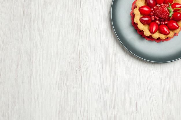 白い机の上に新鮮な果物とおいしいケーキの上面図