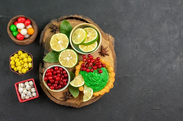 暗い背景の甘いクッキーパイのない場所に果物やキャンディーとおいしいケーキの上面図