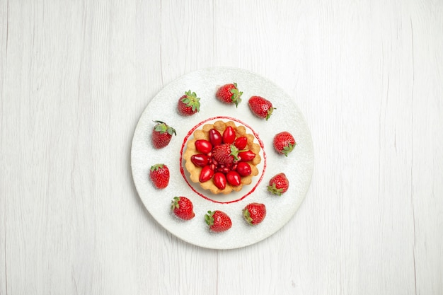 Вкусный торт с фруктами внутри тарелки на белом столе, вид сверху