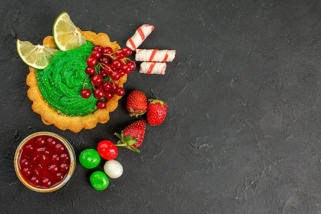 灰色の背景のクッキービスケット砂糖に果物とおいしいケーキの上面図