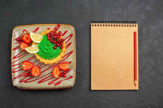 暗い背景のデザートの甘いお茶に緑のクリームとイチゴの上面図おいしいケーキ