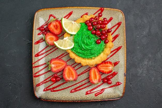 暗い背景の甘いデザートティーに緑のクリームとイチゴの上面図おいしいケーキ
