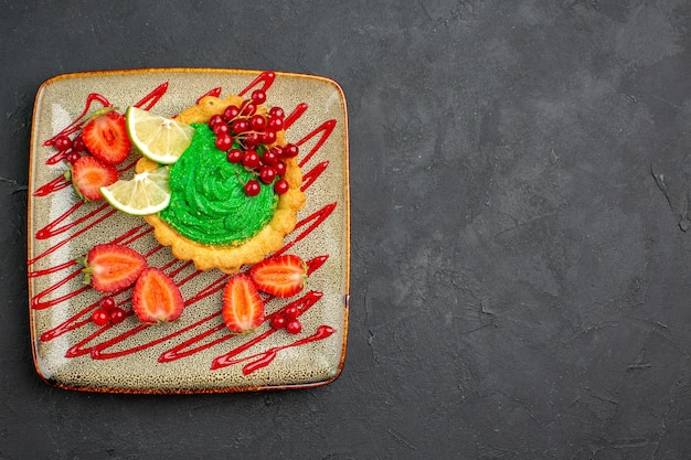 Top view yummy cake with green cream and strawberries on the dark background sweet dessert tea