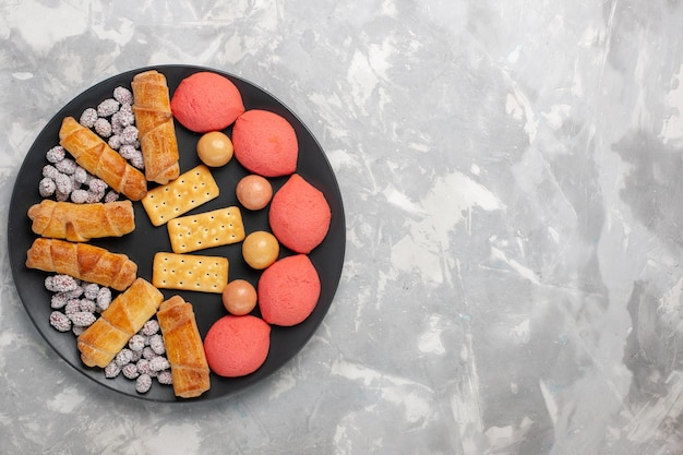 Vista dall'alto deliziose torte con bagel e caramelle sulla superficie bianca chiara