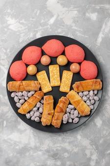 Vista dall'alto deliziose torte con bagel e caramelle sulla scrivania bianca