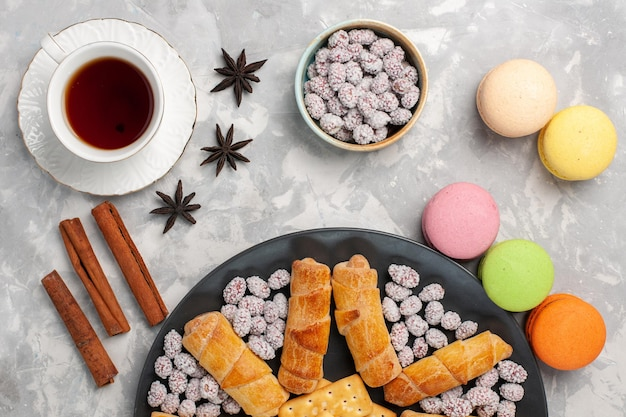 Vista dall'alto deliziose torte con bagel macarons tazza di tè e caramelle su superficie grigio-bianca