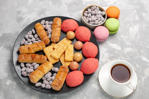 Vista dall'alto deliziose torte con bagel macarons e tazza di tè su superficie bianca grigia