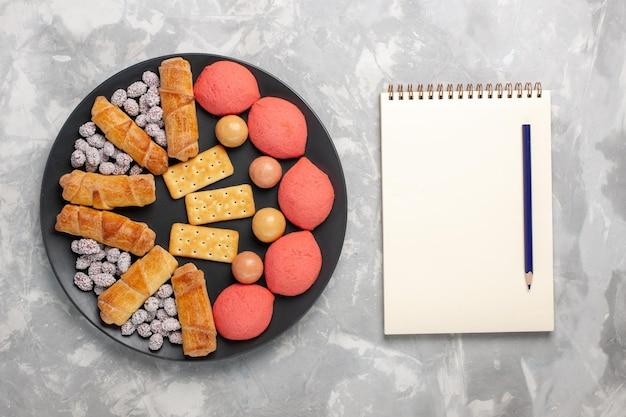 Torte deliziose vista dall'alto con blocco note di bagel e caramelle su superficie bianca