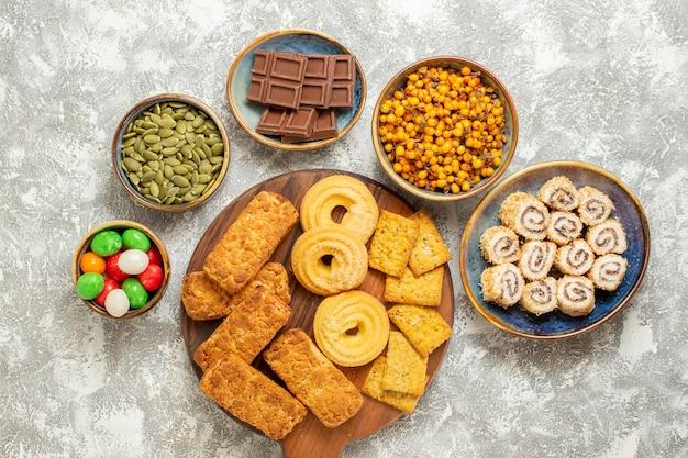 Вид сверху вкусные торты с конфетами и печеньем на белом фоне