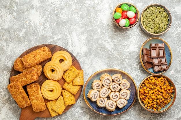 白い背景の上のキャンディーとクッキーとおいしいケーキの上面図