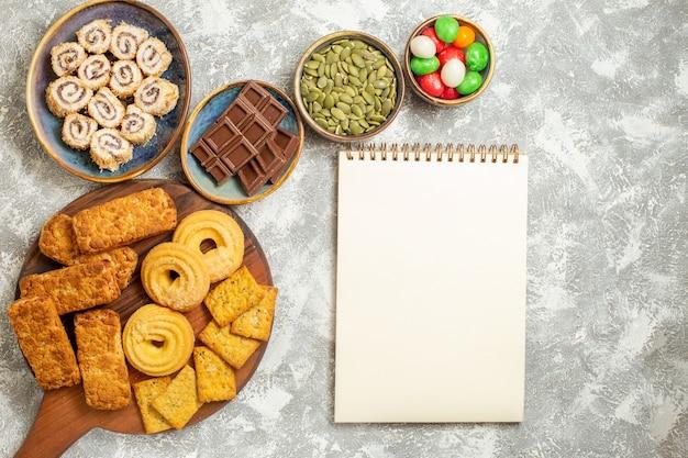 Vista dall'alto gustosissime torte con caramelle e biscotti su sfondo bianco
