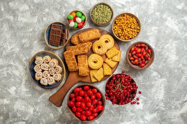 白い背景の上のクッキーと果物とおいしいケーキの上面図