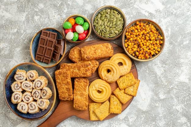 Torte gustose vista dall'alto con biscotti e caramelle su sfondo bianco chiaro