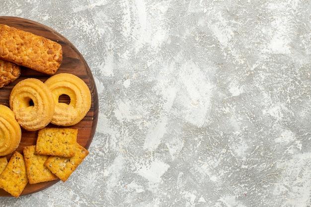 白い背景の上のクラッカーとクッキーとおいしいケーキの上面図