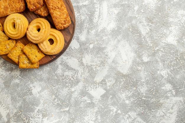 Вкусные торты с крекерами и печеньем на белом полу, вид сверху