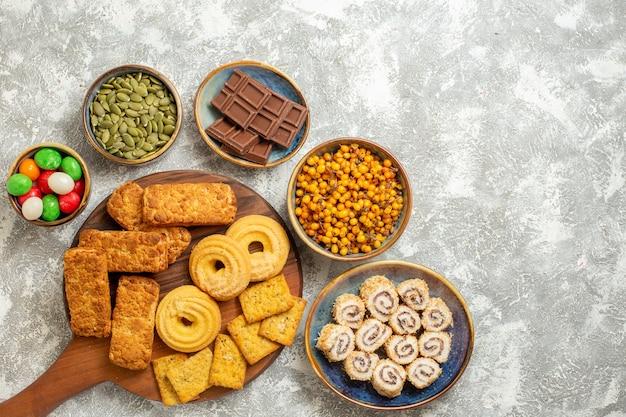 Vista dall'alto gustose torte con cracker e biscotti su sfondo bianco