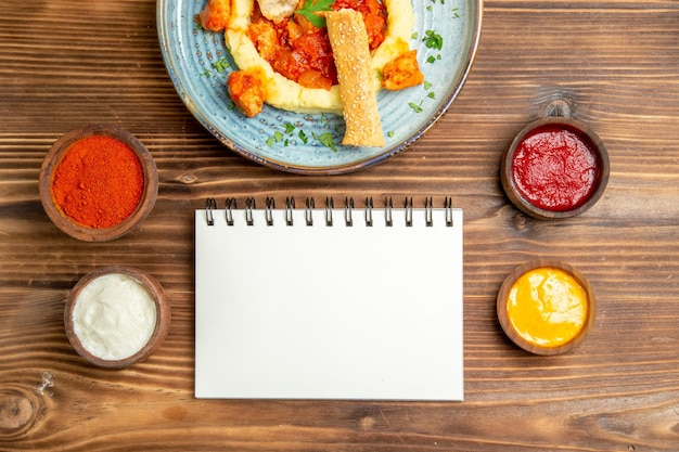 Vista dall'alto di deliziose fette di pollo con purè di patate e condimenti sul tavolo marrone.