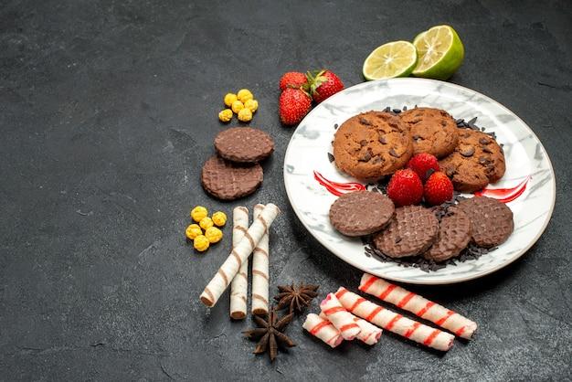 暗い机の上のお茶のための上面図おいしいチョコビスケット甘いクッキーシュガーティー