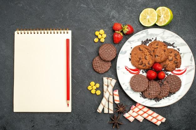 トップビューダークデスクティースウィートクッキーシュガーのお茶のためのおいしいチョコビスケット