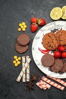 Vista dall'alto gustosi biscotti al cioccolato per il tè sullo sfondo scuro dello zucchero dolce del biscotto del tè