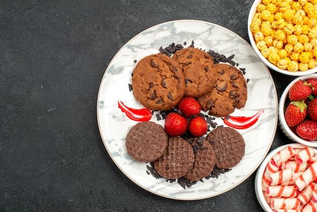 Vista dall'alto yummy choco biscotti con caramelle su sfondo scuro zucchero torta dolce biscotto