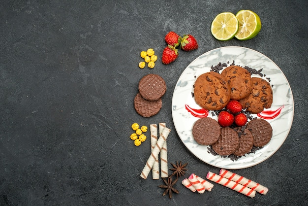 Top view yummy choco biscuits with candies on dark background sweet cookies sugar tea