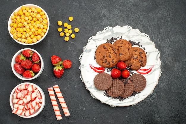 Vista dall'alto gustosi biscotti al cioccolato con caramelle su sfondo scuro dolce zucchero torta biscotto