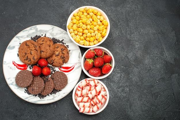 暗い背景にキャンディーと甘いクッキーケーキシュガーの上面図おいしいチョコビスケット