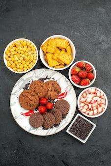 Vista dall'alto gustosi biscotti al cioccolato con diversi snack su sfondo scuro biscotto dolce del tè