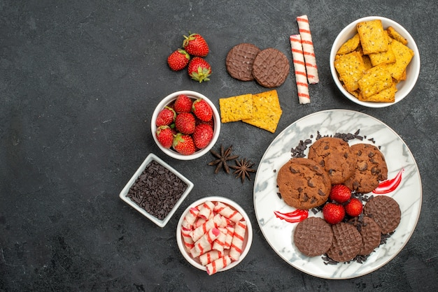 Вид сверху вкусное шоколадное печенье с разными закусками на темном фоне сладкое печенье чай