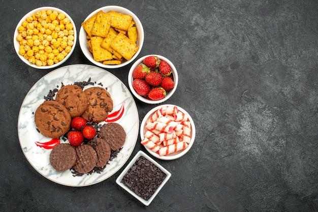 暗い背景のお茶の甘いクッキーの写真にさまざまなスナックとおいしいチョコビスケットの上面図