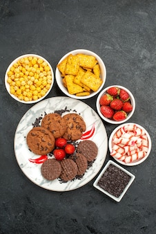 暗い背景のお茶の甘いクッキーにさまざまなスナックとおいしいチョコビスケットの上面図