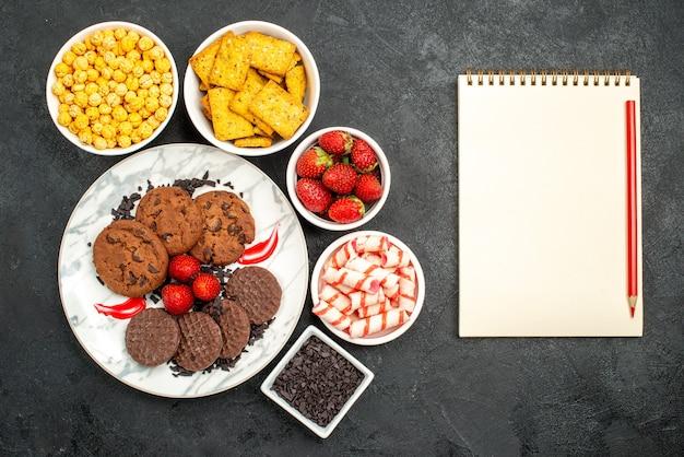 Вид сверху вкусного шоколадного печенья с разными закусками на темном фоне чайное сладкое печенье